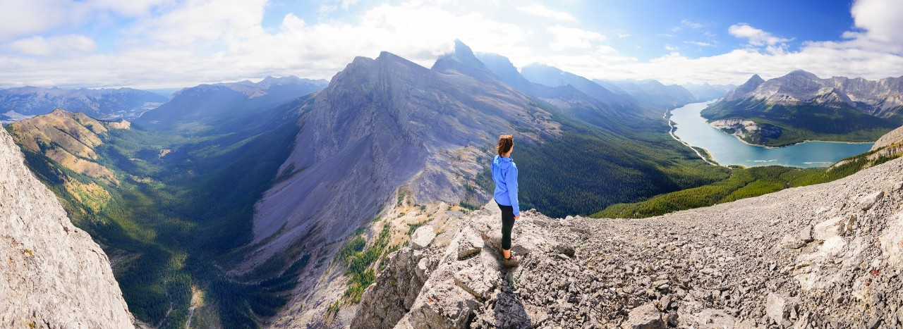 A woman stands on top of a natural feature known as the Rimwall. To the far left is the Bow Valley, followed by the Wind Valley. Mount Lougheed is seen in the center. The Spray Lakes valley is seen on the right.