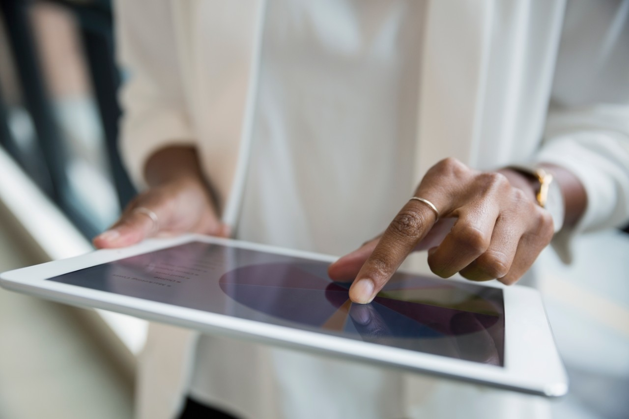 Close up businesswoman reviewing pie chart on digital tablet