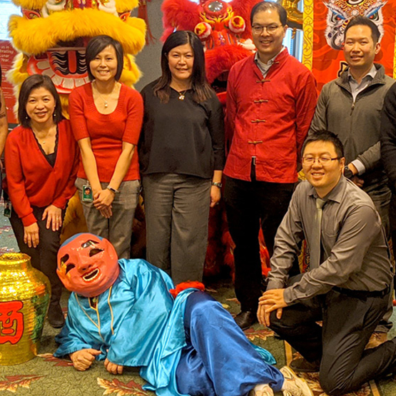 PACES committee members pose for a photo with traditional dancers for Chinese New Year.